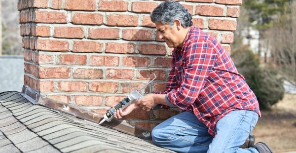 man applying sealant to chimney flashing