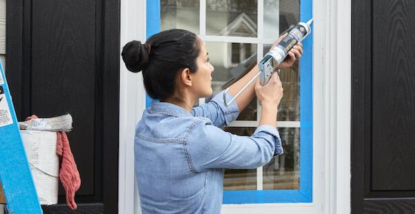 woman sealing around a window